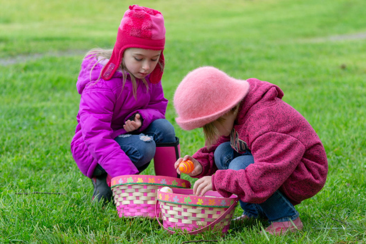 Two Children Inspecting Their Easter Eggs in Their Baskets